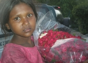 Little girl street vendor selling flowers in Delhi, India