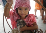 Littlest girl at orphanage and puppy in Cambodia
